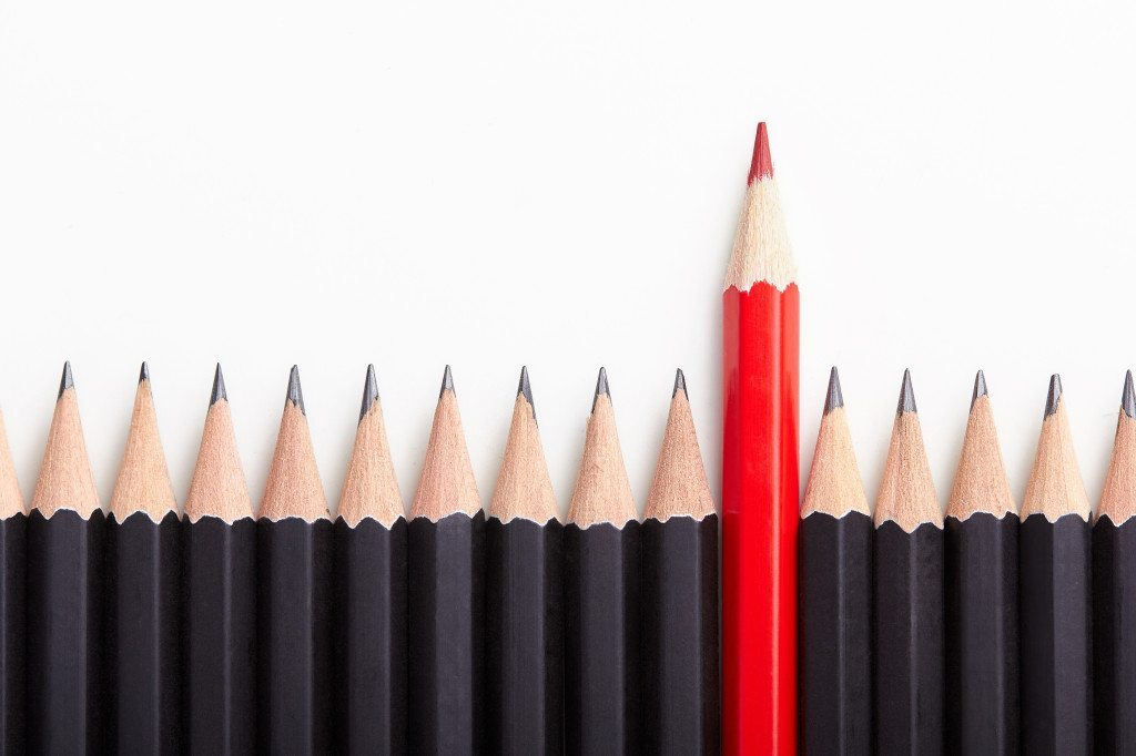 Red pencil standing out from crowd of plenty identical black fellows on white table. Leadership uniqueness independence initiative strategy dissent think different business success concept