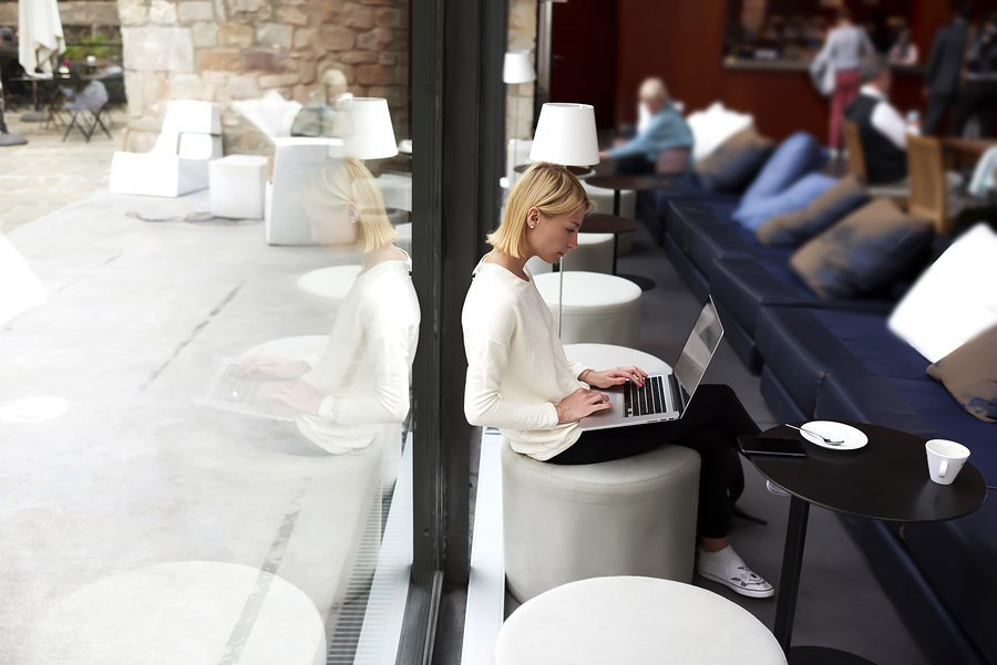 Lovely modern business woman keyboarding on net-book while worki
