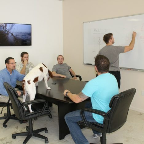 5 Men at a conference table looking at a whiteboard.