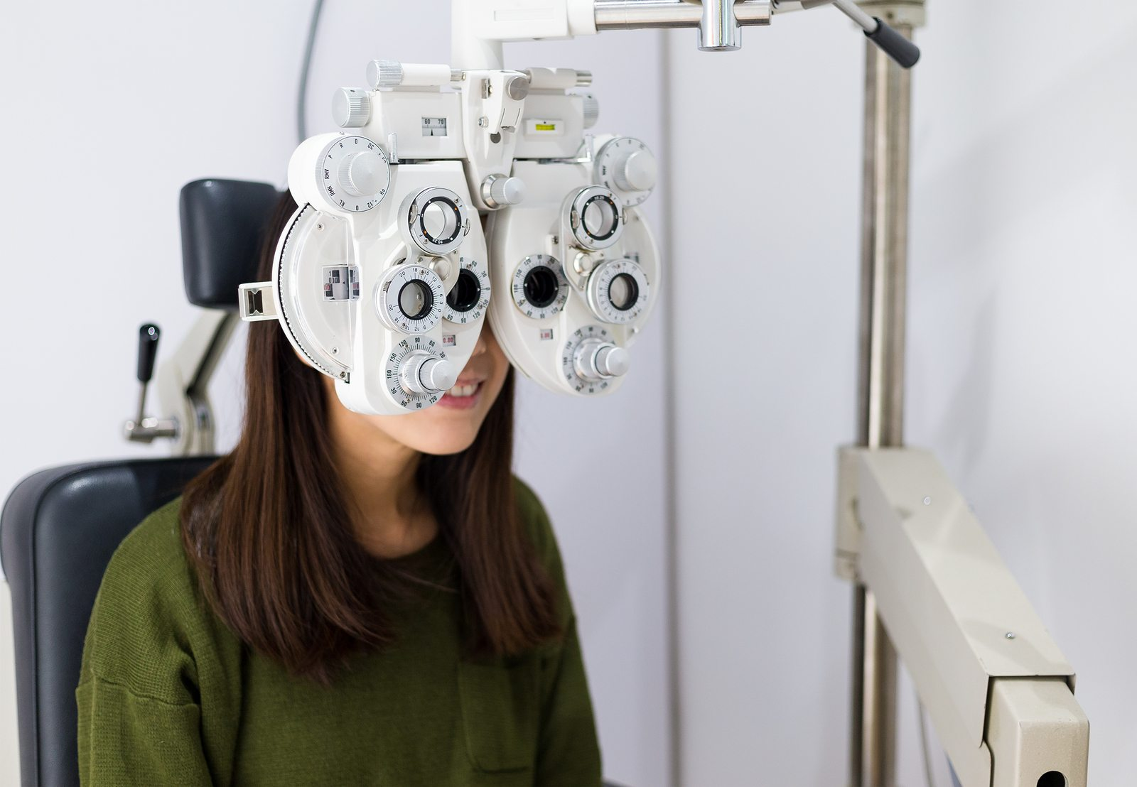 Woman checking on her eye with optometry machine