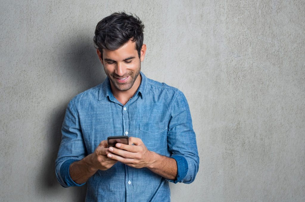 Young man texting message on smart phone isolated on grey background. Using Apps on the phone.