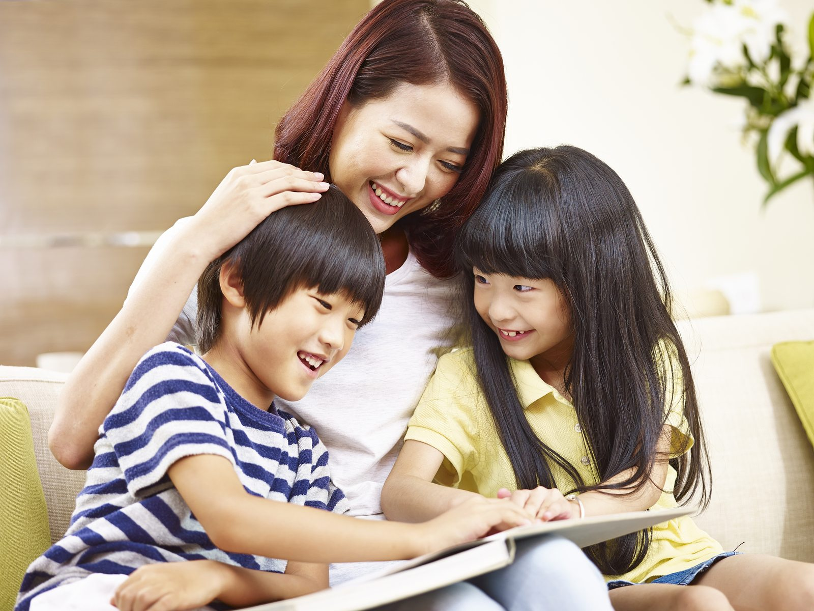 young mother sitting on couch at home reading story to two little children.