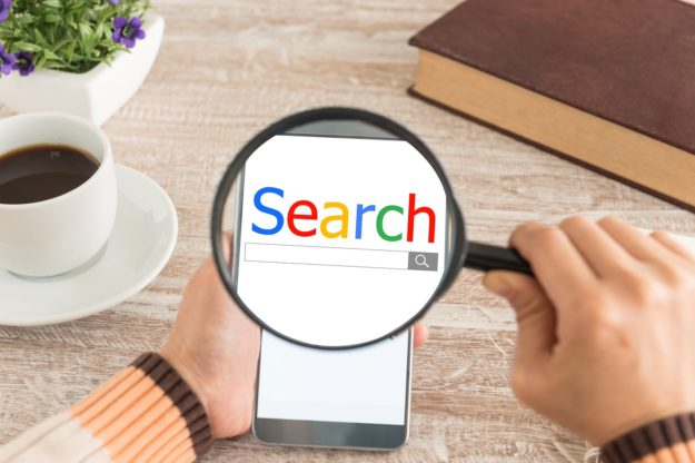 search engine concept image with phone and magnifying glass