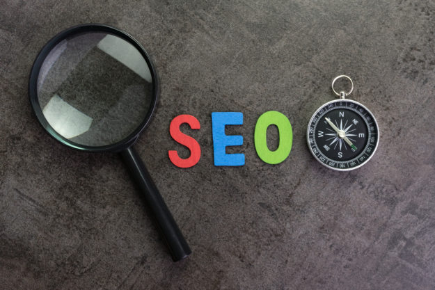 Magnifier glass, colorful alphabet SEO and compass on dark chalkboard background using as SEO Search engine optimization concept.