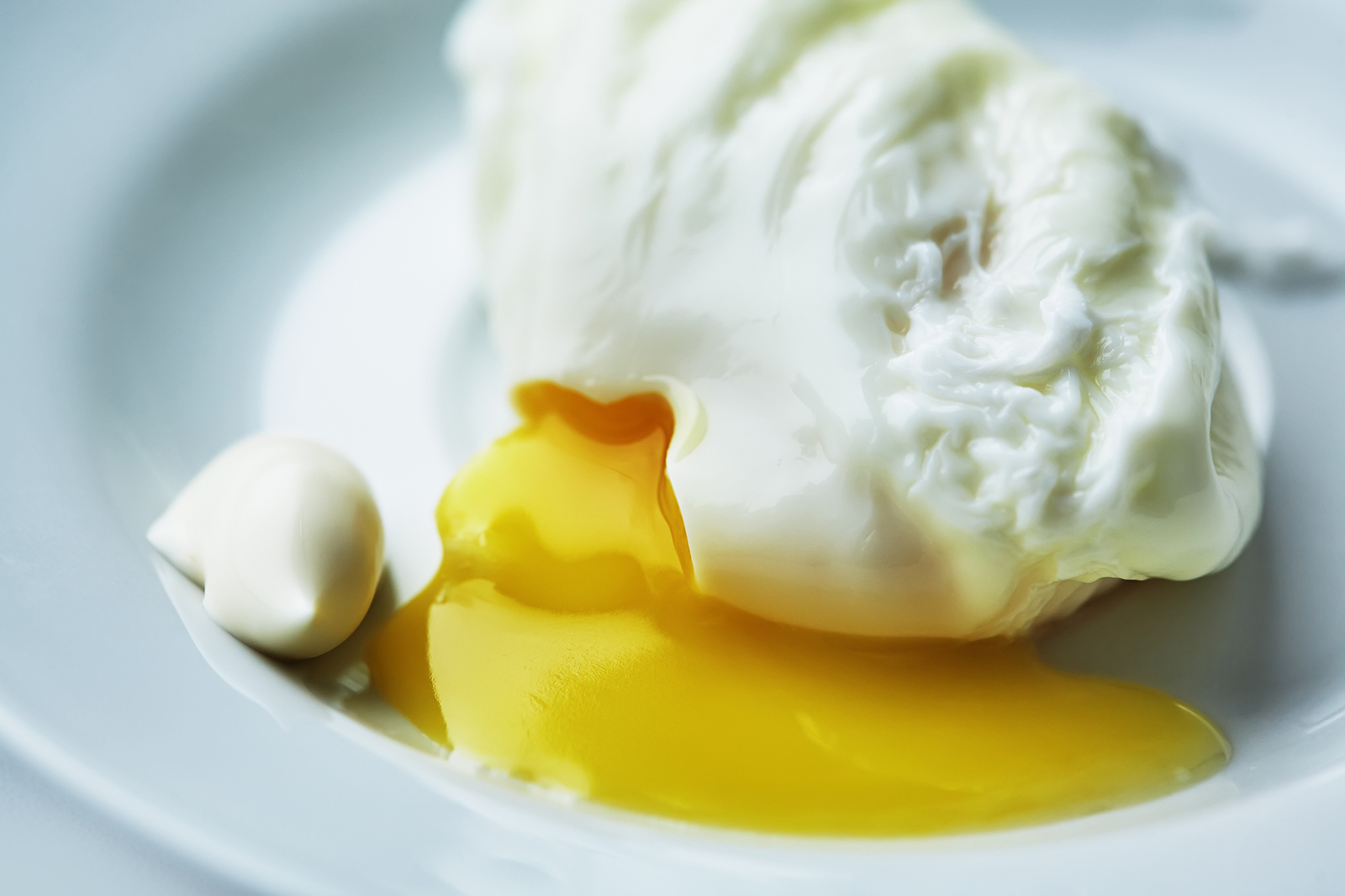 The liquid yolk flows from the poached egg onto a white plate